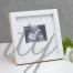 Бяла рамка за снимката от ехографа с надпис Baby scan It's a girl